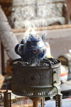 """Tea:  A kettle heating for tea time.  """"The cup of tea on arrival at a country house is a thing which, as a rule, I particularly enjoy. I like the crackling logs, the shadedlights, the scent of buttered toast, the general atmosphere of leisured cosiness.""""  ---P.G. Wodehouse, """"The Code of the Woosters."""""""