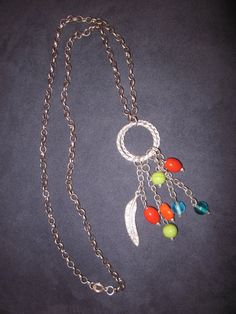 This is such a fun necklace! It's a silver rope link about 27 inches long, that has a double ring (1 inch round) hanging at the center and from the rings hangs a silver feather and colored beads in vibrant orange, green, and blue, the longest length (the feather) measures down another 1-1/2 inches for a total length of 29-1/2 inches. A very versatile piece.
