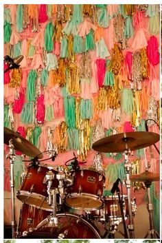 yarn tassle/tinsel wall behind a band! so much fun.