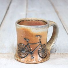 This mug has a hand-carved bicycle design on one side.    It will hold 12 liquid ounces. Wheel-thrown in our Vermont studio from white stoneware clay,