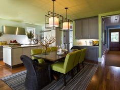 Green walls and chairs with gray cabinetry. Love the open concept kitchen/dining room and the lights and candles are great. Not wild about the black patio chairs though...