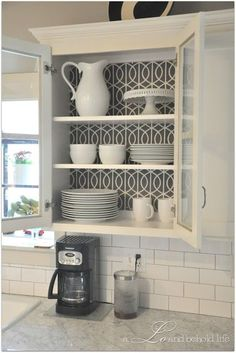 Add a liner to your kitchen cabinet. It not only looks lovely, the contrasting paper (or fabric) makes lighter-hued items stand out.
