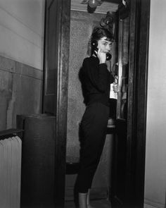 Belgian-born actor Audrey Hepburn (1929-1993), holding a Western Union telegram, stands in a telephone cabin with a receiver to her ear on the set of director Billy Wilder's film, 'Sabrina', New York