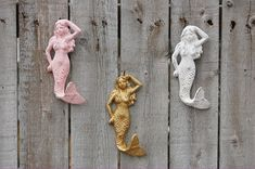 Set of 3 cast iron mermaid shaped wall hooks. Hand painted in soft pink, gold and white, lightly distressed and finished with a protective