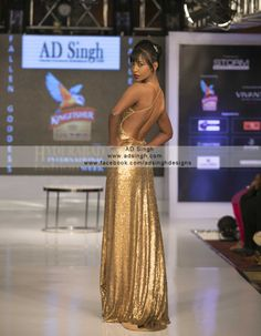 Backless Gold red carpet Gown by AD Singh made in antique gold sequins sheeting with a tail bone deep neckline. A delicate trail makes the entire gown totally red carpet.