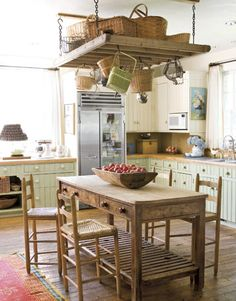 """Cabinetry """"painted the same colors for simplicity,"""" is paired with butcher-block countertops and a marble backsplash. For the kitchen, Megan found a tall antique table, and used an old baker's rack instead of a new pot rack."""