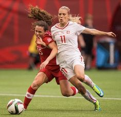 Lara Dickenmann #11 of Switzerland tries to break free from Allysha Chapman #15 of Canada during the FIFA Women's World Cup Canada 2015 Round of 16 match between Switzerland and Canada June, 21, 2015 at BC Place Stadium in Vancouver, British Columbia, Canada.