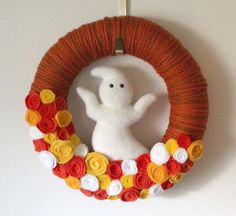 Perfect for Halloween or even fall if you take out the ghost. Fall colors are rich and warming.  Yarn and felt Halloween wreath featuring a ghost and candy corn colored rosettes, 14-inch size.     The base is a 14-inch straw wreath form, wrapped with several shades of orange yarn. In the center sits a cute flocked white ghost, along with lots of my handmade felt and fleece flowers in orange, yellow, and white colors. This wreath can hang on a wreath hanger as shown, or hang on a nail using…