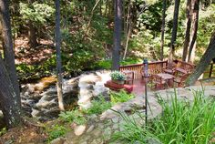Waterfall river deck and garden, gorgeous secluded private landscaping with decking over rushing water, stone pathway, plants, containers, t...