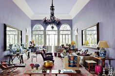 May Daouk - The home is oriented around an expansive antiques-filled living room painted a striking lilac. The table at left displays ceramics found at John Rosselli Antiques. The purple armchairs are from Ann-Morris Antiques, and the large Oushak carpet is 19th century.