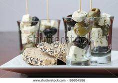 Greek appetizers in small glasses with black and green olives and feta cheese by IngridHS, via ShutterStock