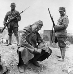 Two Chinese soldiers guarding a captured Japanese soldier, Changde, Hunan Province, China, Nov-Dec 1943.
