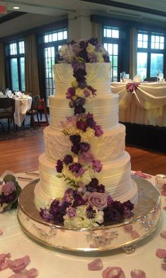 wedding cake- Four Circle shaped tiers with white icing and a mix of purple flowers on top cascading down the side of the cake