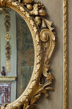 Detail of an oval pier-glass in the Queen's Bedchamber at Ham House, one of a pair by supplied by William Bradshaw, c.1743. It reflects a carved and gilded garland by John Bullamore dating from the 1670s. ©National Trust Images/John Hammond