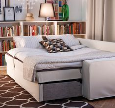 IKEA sofa-bed made up as a double bed at night VILASUND/ MARIEBY $849.00  IKEA Billy bookcases behind ($39.99) & floor lamp behind