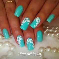 A bright spring manicure made by turquoise gel lacquer, decorated with snow-white flowers. This contrasting combination of colors allows you to create an i