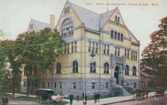 Police headquarters, at the corner of Crescent St. and Ottawa Ave., showing the stone and brick facade probably in the original colors. The lower portion of the building, the front stairs, and the arches over the windows are of grey stone while the walls