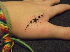 Sparkling tattoo of shooting black stars inked on hand.