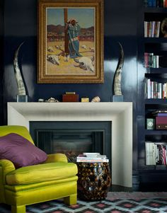 Veronica Swanson Beard Manhattan Apartment: verneer walls, sculptural marble tusks on streamlined chrome fireplace mantle, chartreuse armchair with purple pillow, built in bookcases and patterned rug