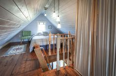 Even though the ceilings are low, this attic loft makes great sleeping quarters for guests. The couple painted the wood-paneled walls in the same whitewash as in the main areas on the first floor to keep the space bright. Through the small window is a view of the marina.  Wall paint: White Chocolate, Benjamin Moore