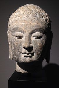 Very finely carved head of a Buddha from the Northern Qi Dynasty, Shandong Province, 550 - 577 A.D. This period represents the height of early Chinese Buddhist sculpture, and strongly reflects the Indian Gupta style. The face of this Buddha is very classical in its regular features and beautiful curving eyes and lips, and arched brows.