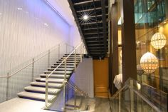 Glass, Metal, and Smooth Stone Staircase of Orchard Central, Singapore. Photo by Mahisa