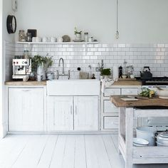 White-washing every single surface cleverly brings a modern lightness and unity to this kitchen while emphasising the farmhouse ruggedness of the worn wooden work surfaces. Try salvage yards for finds such as the central butcher's block - Salvoweb has several from around the UK.