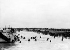 Troops of the Canadian 9th Infantry Brigade part of 3rd Division carrying their bicycles ashore from landing craft LCL 299 , JUNO BEACH 6/6/44