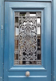 Elaborate ironwork door glass grille with scrollwork and geometric corners - Paris 2015
