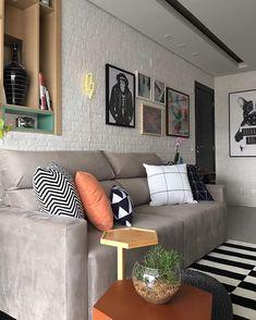 Paleta de cores: branco, cinza, preto, madeira e alguns toques de cor (laranja e azul) Atenção para quadros, almofadas e neon na parede.