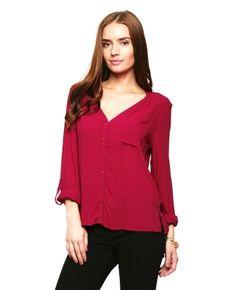 Blusa Anna Flynn.Blusa color vino, superficie lisa, escote en \