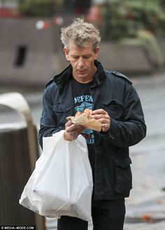 Careful!He juggled two plastic bags on his arm as he continued to eat the pie