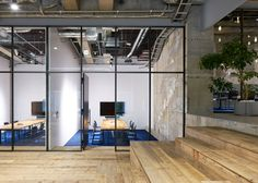 Multi-levelled surfaces of polished concrete, wood and white gravel mark out the different areas within this open-plan Tokyo office.