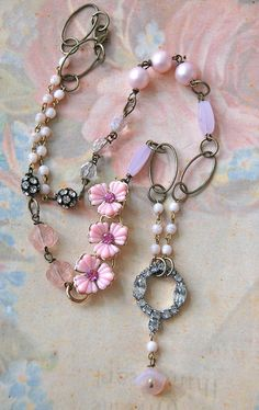 This is a 22 vintage style necklace. It is adorned with assorted vintage glass beads,old pearls, repurposed vintage pink flower links,vintage glass rosarybeads and rhinestone beads with an antique brass chain. The pendant is a repurposed rhinestone finding with a glass pink flower bead