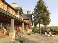 Our clients asked us to design an Arts and Crafts style home that capitalized on their site's mountain views. The residence's clean lines, natural materials and muted color palette are suggestive of the Mission style. Well-crafted details, such as square tapered columns supported by stone bases, wide eaves and exposed rafters, further reveal its Arts and Crafts roots. Porches and sweeping flagstone terraces open the house to lovely Blue Ridge vistas.