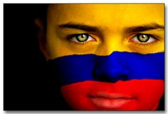 Portrait of a boy with the flag of Colombia painted on his face.