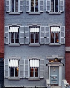 Superchic townhouse with monotone paint, striped awnings and European style shutters that frame the windows