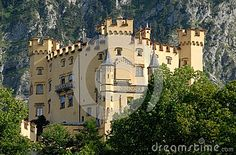 Photo taken at Hohenschwangau Castle in Bavaria (Germany). In the picture you see two facades, the castle of King Ludwig II of Bavaria, forming a triangle, photographed from the road below leading to the town of Fussen. The base of the building is hidden behind the trees and against a backdrop of mountain rocks.