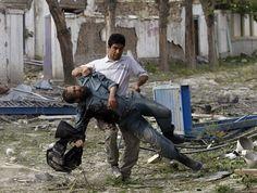 Policial afegão ferido é carregado do local de uma explosão em Cabul nesta sexta-feira (24) (Foto: Omar Sobhani/Reuters)
