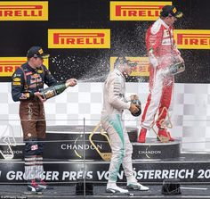 The top three drivers celebrate with champagne on the podium following a controversial Aus...