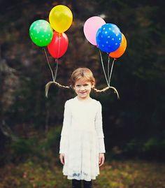 Niña con el cabello sujetado por globos