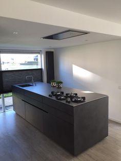 Een fraaie keuken van beton. De aparte greeploze lijn zorgt voor de extra balans in de keuken. De deuren zijn aan de onderzijde langer gemaakt waardoor het lijk alsof je een hele lage plint hebt, maar zo kan je wel de juiste hoogte van het werkblad bepalen. Het gaaft ook meer de robuuste uitstraling. Het RVS werkblad met Pitt-Cooking maakt het af.