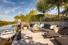 Moderne loungeset aan het water op een mooie houten vlonder.