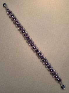 Amethyst and White Glass Pearl bead Bracelet with Silver seed bead embellishments. Silver Magnetic closure. Measures about 7 1/2 inches long and about 1/2 inch wide. Very feminine.