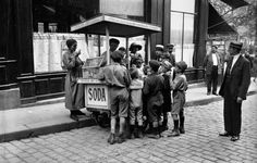 An ice-cream vendor selling sodas and sweets to children on the city streets, 1925.