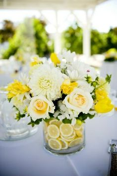 White and yellow flowers in a vase of lemons for a #centerpiece.