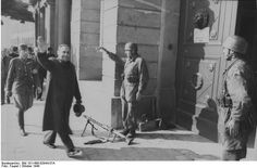 Budapest, Hungary, Oct 1944: A smiling Ferenc Szálasi, new prime minister and leader of the Nazi Arrow Cross organization, arrives at the ministry of defense after the Germans occupied Hungary. He is escorted by one of his senior Arrow Cross officers. The sentries at the gate are German paratroopers. Szálasi was executed in 1946 for his collaboration with the Germans.