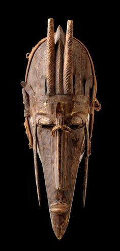 Mask kore from the Marka people of Mali carved with a narrow face with elongated chin, crowned by vertical protruding horns, the long nose bridge accompanied by staff-like metal projections, nearly the whole face coated with punched copper sheetremains of fabric; the Marka, a mixture of the Peul and the Moors are forming an individual group within the Mande (Soninke). All along the Niger this mask type is used for ceremonies associated with fishing and agriculture. H: 46 cm