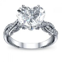 Prepare your eyes for the luscious visual feast in this out of this world diamond engagement ring. A real head turner, this spotless piece features a very remarkable Brilliant-cut diamond as the focus. Dazzling Brilliant Round cut diamonds are pave set around it creating a halo design. The round diamonds continues down the superb open style shank to enthrall your eyes. Alluring side cutouts and d