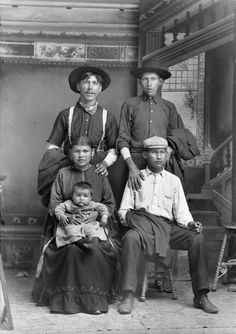 A studio portrait of a group of Native Americans in front of a painted backdrop. A woman in a dress holds an infant in her lap, a man stands behind her, and two boys, one standing and one seated next to them. All the men wear hats, and are holding their suit jackets. One man is smoking.